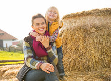 Smiling mother and child sitting on haystack Stock Image