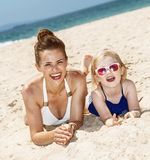 Smiling mother and child in swimsuits laying on sandy beach. Family fun on white sand. smiling mother and child in swimsuits laying on sandy beach on a sunny day stock photography