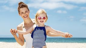 Smiling mother and child in swimsuits playing at sandy beach. Family fun on white sand. Smiling mother and child in swimsuits playing at sandy beach on a sunny royalty free stock images