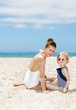 Smiling mother and child in swimsuits sitting at sandy beach Royalty Free Stock Image