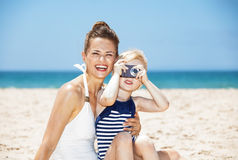 Smiling mother and child taking photos with camera at beach Royalty Free Stock Photos