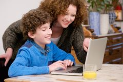 Smiling mother and child using laptop at home Stock Photography