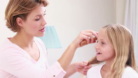 Smiling mother combing hair of daughter stock footage