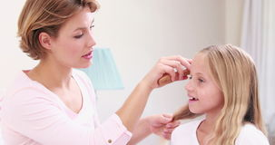 Smiling mother combing hair of daughter stock video