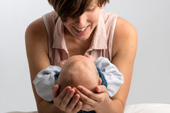 Smiling mother cradling her newborn baby Royalty Free Stock Images
