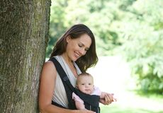 Smiling mother with cute baby in sling Royalty Free Stock Photos