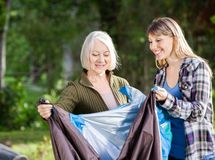 Smiling Mother And Daughter Assembling Tent In Royalty Free Stock Photography
