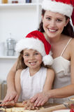 Smiling mother and daughter baking Christmas cakes Stock Photo