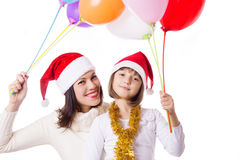 Smiling mother with daughter with balloons and Christmas hats Stock Images