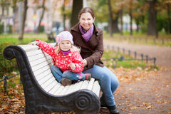 Smiling mother and daughter on a bench Stock Photography