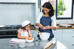 Smiling mother and daughter breaking eggs Royalty Free Stock Photography