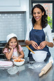 Smiling mother and daughter breaking eggs Stock Photo