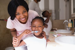 Smiling mother with daughter brushing teeth in bathroom at home stock image