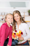 Smiling mother and daughter with a bunch of roses Royalty Free Stock Images
