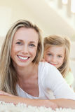 Smiling mother and daughter on the carpet Royalty Free Stock Photo