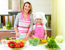 Smiling mother and daughter cooking a salad. Stock Photo