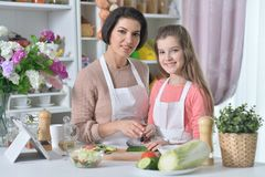 Portrait of smiling mother and daughter cooking together at kitchen stock images