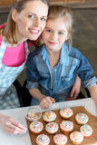 Smiling mother and daughter with cupcakes on board Stock Images