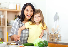 Smiling mother and daughter cutting vegetables Royalty Free Stock Images