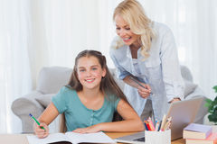 Smiling mother and daughter doing homework Stock Photo