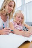 Smiling mother and daughter drawing together Royalty Free Stock Images
