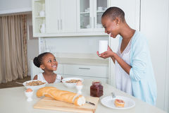 Smiling mother and daughter eating together stock photo