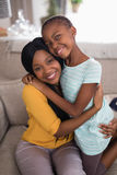 Smiling mother and daughter embracing on sofa at home Stock Photography