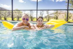 Smiling Mother and Daughter floating on an inflatable raft in the swimming pool Stock Photos