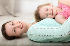 Smiling mother and daughter on the floor Stock Photo