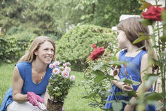 Smiling mother and daughter gardening flowers in the garden Stock Image