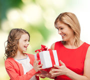 Smiling mother and daughter with gift box. Family, child, holiday and party concept - smiling mother and daughter with gift box Royalty Free Stock Image