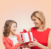 Smiling mother and daughter with gift box. Family, child, holiday and party concept - smiling mother and daughter with gift box Royalty Free Stock Images