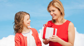 Smiling mother and daughter with gift box. Family, child, holiday and party concept - smiling mother and daughter with gift box Stock Images
