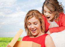 Smiling mother and daughter with gift box. Family, child, holiday and party concpt - smiling mother and daughter with gift box Stock Images