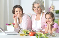 Mother, daughter and grandmother cooking together Royalty Free Stock Photos