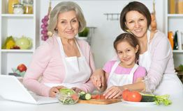 Mother, daughter and grandmother cooking together Royalty Free Stock Photography