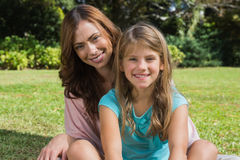 Smiling mother and daughter on the grass. In park looking at camera Royalty Free Stock Image