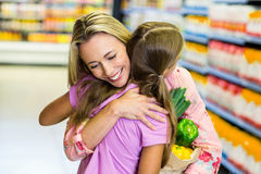 Smiling mother and daughter with grocery bag hugging Royalty Free Stock Photo