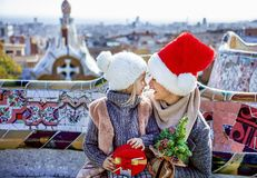 Smiling mother and daughter at Guell Park looking at each other. Winter wonderland in Barcelona at Christmas. Portrait of smiling trendy mother and daughter Royalty Free Stock Image