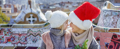 Smiling mother and daughter at Guell Park looking at each other. Winter wonderland in Barcelona at Christmas. Portrait of smiling trendy mother and daughter Royalty Free Stock Images