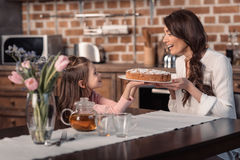Smiling mother and daughter holding cake in kitchen, mother`s day holiday concept Royalty Free Stock Image