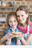 Smiling mother and daughter holding plate with cupcakes Royalty Free Stock Photography