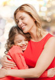 Smiling mother and daughter hugging. Family, child and happiness concept - hugging mother and daughter Stock Photography