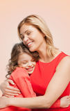 Smiling mother and daughter hugging. Family, child and happiness concept - hugging mother and daughter Stock Image