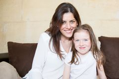 Smiling mother and daughter hugging on sofa. Happy smiling mother and daughter hugging on sofa Stock Photography