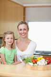 Smiling mother and daughter in the kitchen Stock Photography