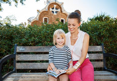 Smiling mother and daughter listening audioguide in Park Guell Stock Photos