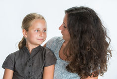 Smiling mother and daughter looking into each other on a white b Stock Images