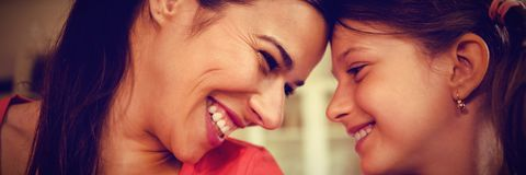 Smiling mother and daughter looking face to face. At home Stock Photos