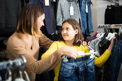 Smiling mother and daughter are looking for pairs of jeans. In children's clothing shop Royalty Free Stock Photography